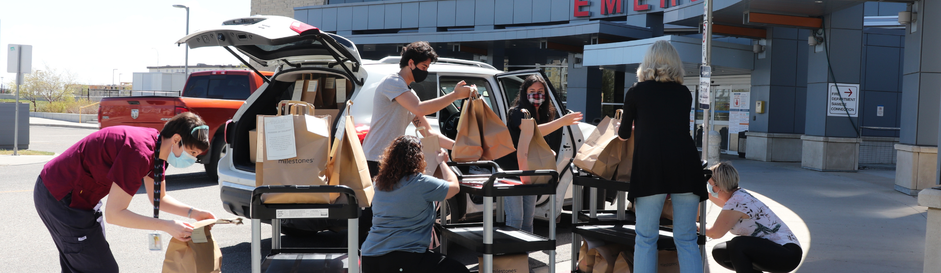 Several people loading donations in front of a hospital