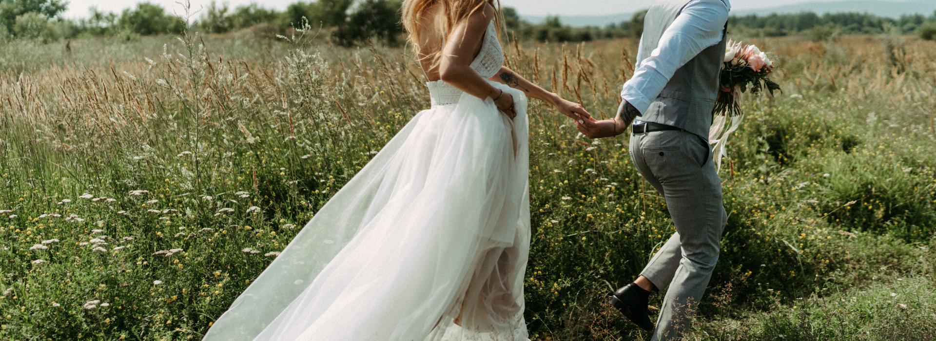Woman and man in wedding attire running through field