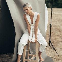 Girl in white outfit posing on chair