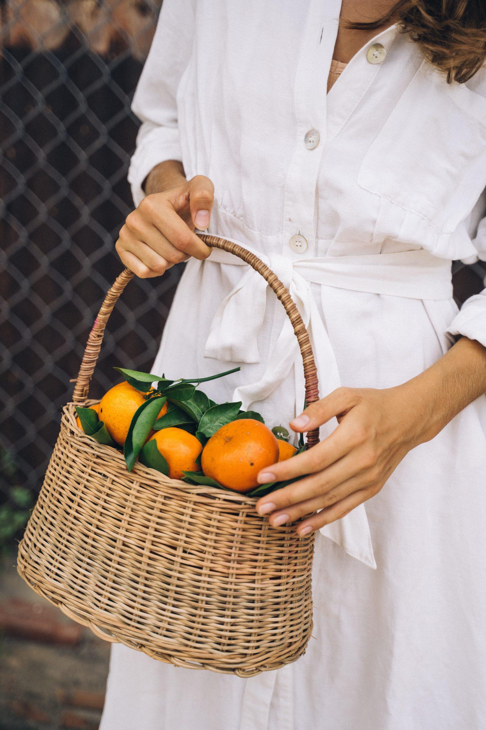 White flowy dress and basket of mandarins