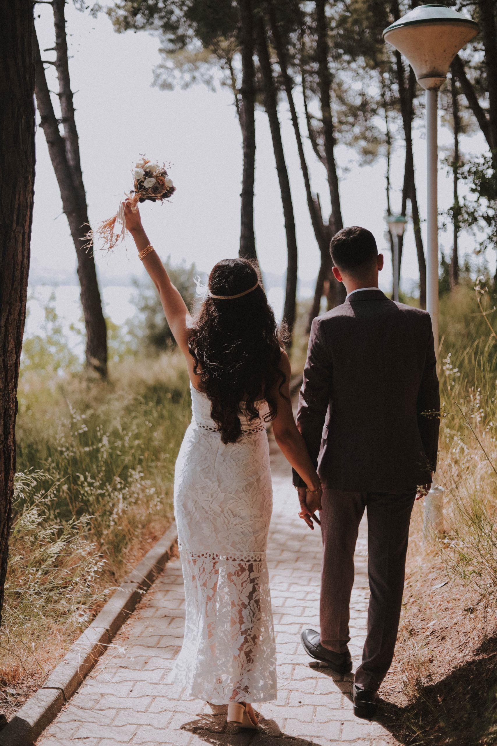 Wife and husband walking hand-in-hand down a path.. Wife holding bouquet in the air