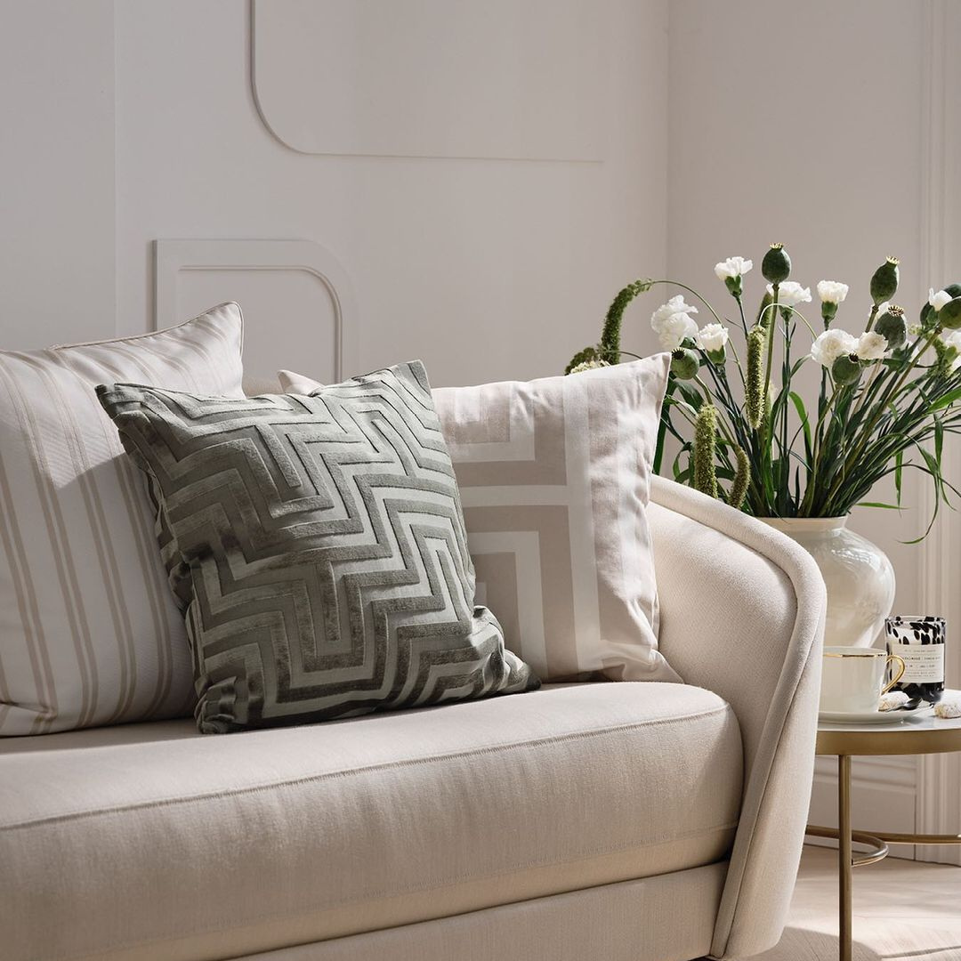 Geometric patterned pillows clustered on a couch with small end table with flowers