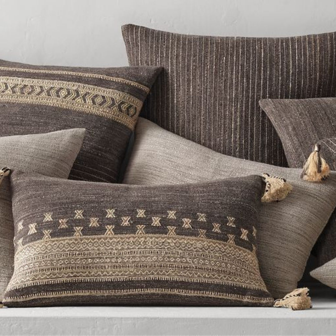 A pile of grey and beige pillows with different prints
