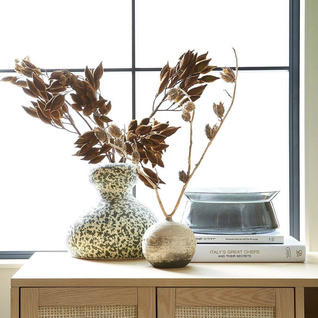 A curvy speckled vase and a small round golden vase sitting on a dresser with a stack of books