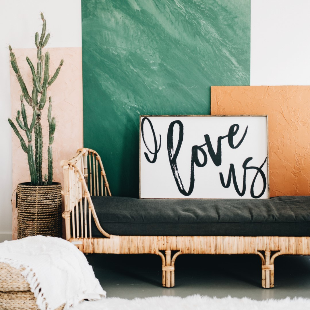 """Frame that says """"I love us"""" resting on the wall with a green and orange canvas"""
