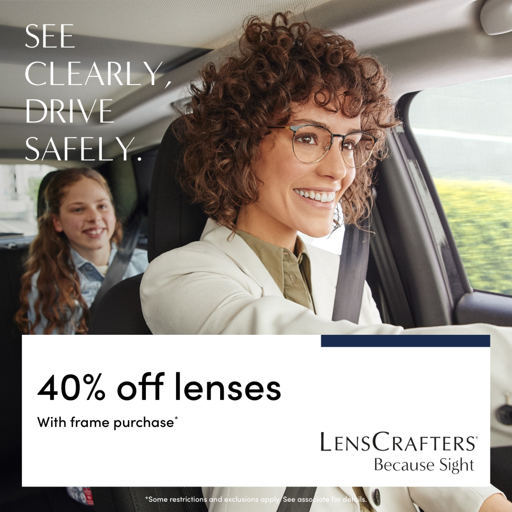 Woman smiling and driving with child sitting in back seat