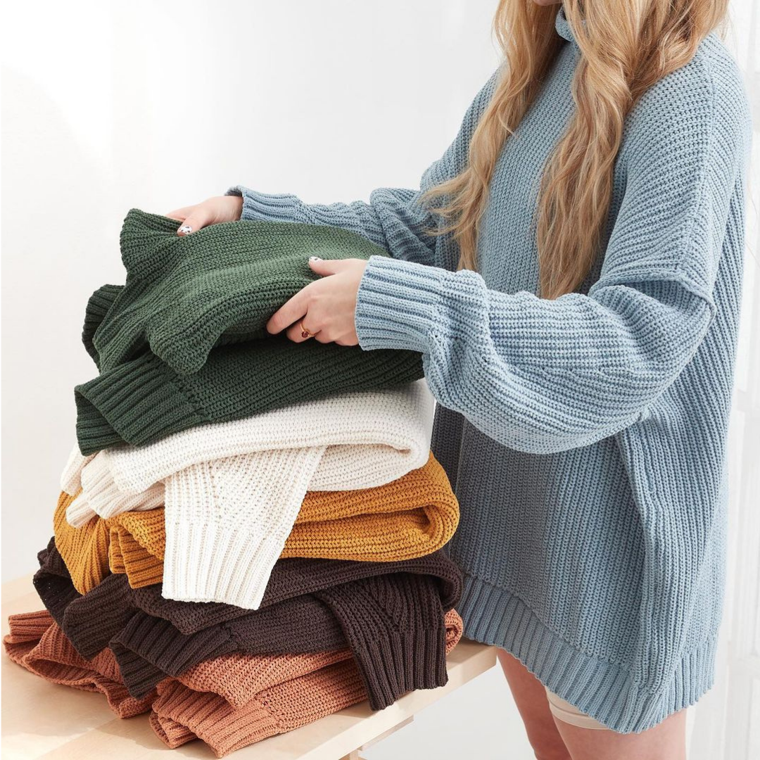 Woman folding knit sweaters