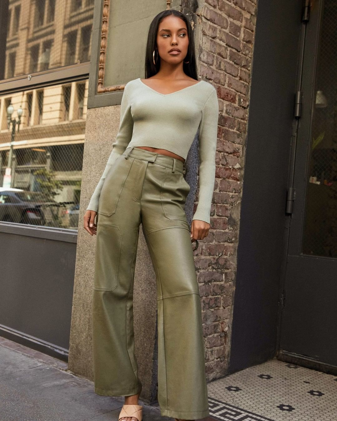Woman in a green outfit and leather pants